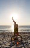 mujer que se coloca en sus manos en la playa Fotografía de archivo libre de regalías
