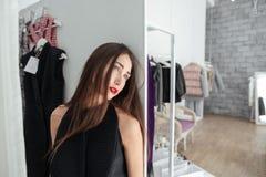 Mujer que se coloca en tienda de ropa Imagen de archivo libre de regalías