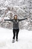 Mujer que se coloca en un arbolado nevoso con sus brazos separados extensamente Foto de archivo