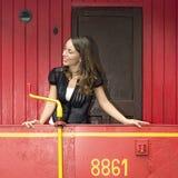 Mujer que se coloca en un Caboose rojo imagenes de archivo