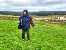 Mujer que se coloca en una colina ventosa Foto de archivo