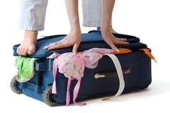 Mujer que se coloca en una maleta Fotografía de archivo