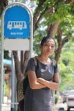 Mujer que se coloca en una parada de autobús imágenes de archivo libres de regalías