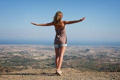 Mujer que se coloca en una tapa de la montaña Imagen de archivo
