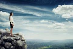Mujer que se coloca encima de la montaña Imagen de archivo libre de regalías