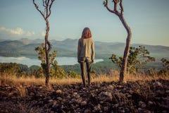 Mujer que se coloca entre dos árboles Imagen de archivo libre de regalías