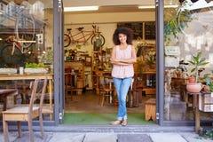 Mujer que se coloca feliz en la entrada de su cafetería foto de archivo libre de regalías