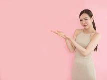 Mujer que se coloca que lleva a cabo su mano que muestra algo en backgr rosado Imágenes de archivo libres de regalías