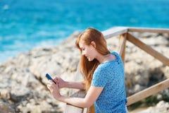 Mujer que se coloca que manda un SMS en su móvil Foto de archivo libre de regalías