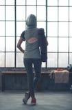 Mujer que se coloca relajante en el gimnasio visto de detrás sudadera con capucha que lleva Fotografía de archivo