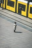 Mujer que se coloca solamente en la calle delante del tranvía/de la tranvía tr Fotografía de archivo