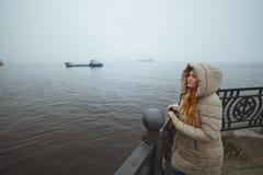 Mujer que se coloca solamente en la costa de mar y que mira en la nave Flor en la nieve Esposa del ` s del marinero imagen de archivo libre de regalías