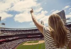 Mujer que se coloca y que anima en un juego de béisbol Imagen de archivo