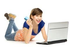 Mujer que se considera de la tarjeta de crédito usando la computadora portátil Fotografía de archivo libre de regalías