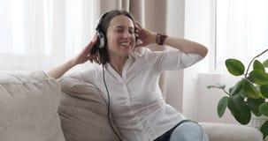Mujer que se divierte mientras que música que escucha en los auriculares en casa metrajes