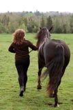 Mujer que se ejecuta con el caballo fotografía de archivo