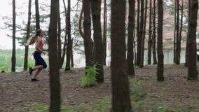 Mujer que se ejecuta en el bosque almacen de video