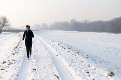Mujer que se ejecuta en la nieve Imágenes de archivo libres de regalías