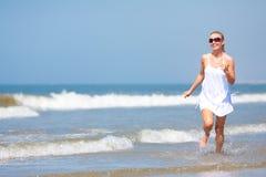 Mujer que se ejecuta en la playa Imagen de archivo libre de regalías