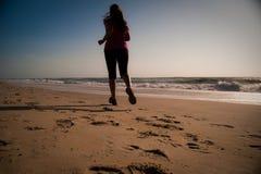 Mujer que se ejecuta en la playa Fotos de archivo libres de regalías