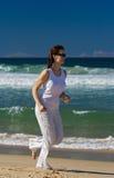 Mujer que se ejecuta en la playa imagen de archivo
