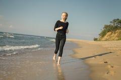Mujer que se ejecuta en la playa Foto de archivo