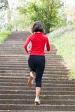 Mujer que se ejecuta en las escaleras del parque Foto de archivo
