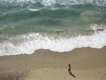 Mujer que se ejecuta en una playa fotografía de archivo
