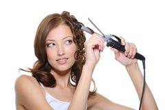 Mujer que se encrespa el pelo con el rodillo Imagen de archivo libre de regalías