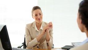 Mujer que se entrevista con sonriente y sacudida de la empresaria de su mano almacen de video