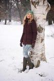Mujer que se inclina contra árbol en invierno Fotos de archivo libres de regalías