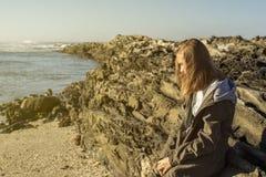 Mujer que se inclina contra rocas en la playa foto de archivo libre de regalías
