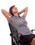 Mujer que se inclina detrás en una silla Fotos de archivo libres de regalías
