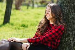 Mujer que se inclina en el árbol al aire libre Fotos de archivo