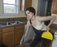 Mujer que se inclina en la escoba Imagen de archivo