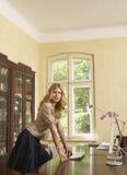 Mujer que se inclina en la tabla del estudio en casa Fotografía de archivo libre de regalías