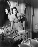 Mujer que se inclina en su tabla de la vanidad (todas las personas representadas no son vivas más largo y ningún estado existe Ga foto de archivo