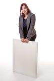 Mujer que se inclina en una muestra en blanco con sus manos Imagen de archivo libre de regalías