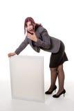 Mujer que se inclina en una muestra en blanco con sus manos contra un CCB blanco Imágenes de archivo libres de regalías