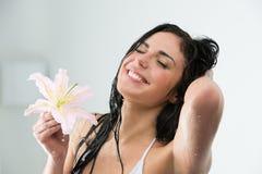 Mujer que se lava con la sonrisa feliz, flor del lirio Imagen de archivo libre de regalías