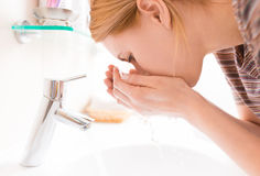 Mujer que se lava la cara con el agua potable foto de archivo libre de regalías