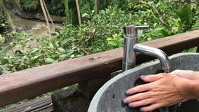 Mujer que se lava las manos afuera con una visión tropical hermosa Concepto de la frescura y de la ecología Isla de Bali almacen de metraje de vídeo