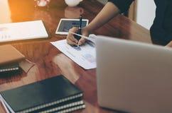Mujer que se levanta en el escritorio y el cierre de trabajo de la mano del documento de la escritura Foto de archivo