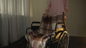 Mujer que se lleva la silla de ruedas vacía, pensando en madre, dolor para querido almacen de video
