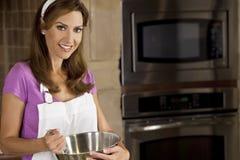 Mujer que se mezcla y que cuece al horno en cocina Fotografía de archivo