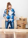 Mujer que se mueve en muebles de la asamblea en el nuevo hogar Foto de archivo libre de regalías
