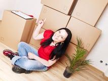 Mujer que se mueve a la nueva casa y que señala el cartón Fotos de archivo