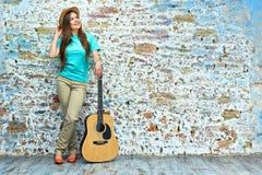 Mujer que se opone con la guitarra a la pared del grunge Foto de archivo