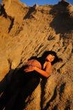 Mujer que se opone a roca Textured en la puesta del sol Foto de archivo
