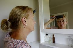 Mujer que se peina el pelo Imagenes de archivo